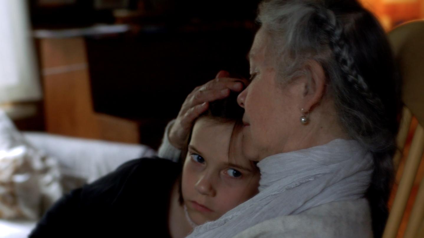 Aamu dans les bras de sa grand-mère, dans Le grand châle d'Aamu